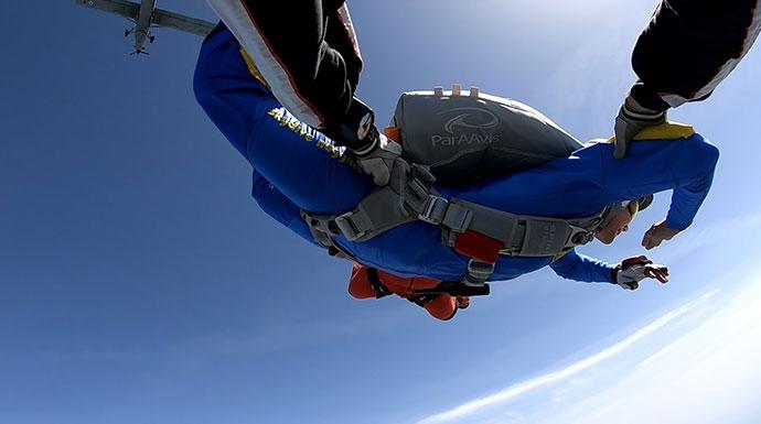instruktor sa dve ruke drzi padobranca prilikom uvezbavanja slobodnog pada