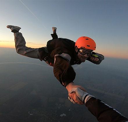 Student i instruktor padobranstva se drže za ruke u toku slobodnog pada nakon iskakanja iz aviona