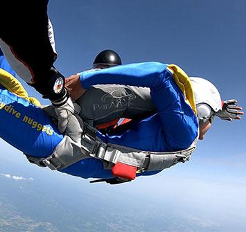 instruktor drzi padobranca dok on vrsi simulaciju otvaranja padobranom