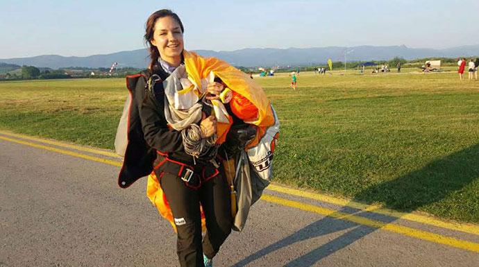 nasmejana devojka nakon izvedenog prvog samostalnog skoka padobranom