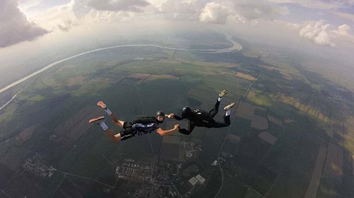 dvoje padobranaca se drzi za ruke prilikom slobodnog pada