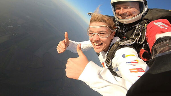 tandem skok instruktor i devojka nasmejani prilikom slobodnog pada