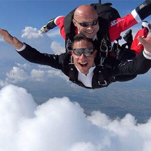 Student i tandem instruktor nasmejani prilikom skakanja padobranom iz aviona
