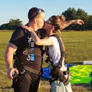 dvoje zaljubljenih ljudi se ljubi nakon skoka padobranom